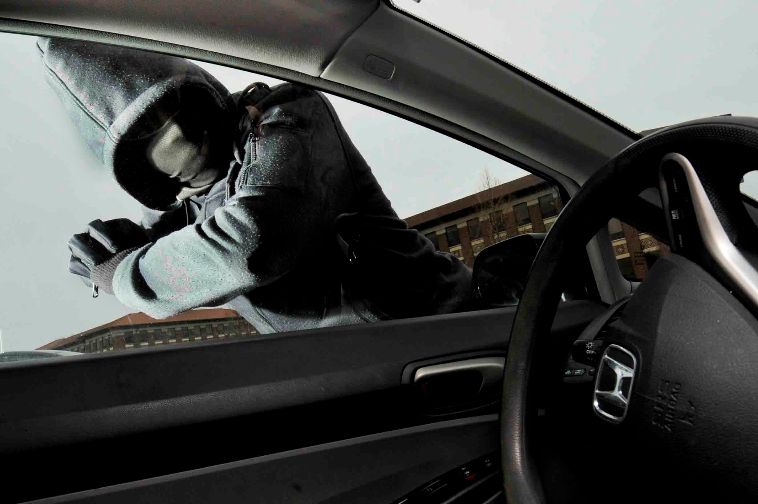 Thief attempting to break car window